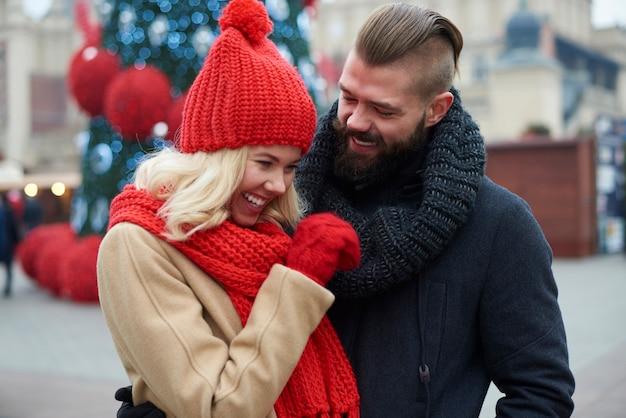 Para zabawnie spędzająca czas na jarmarku bożonarodzeniowym