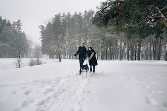 Para zakochanych bawić się z psem Husky w mroźną zimę zimowy dzień