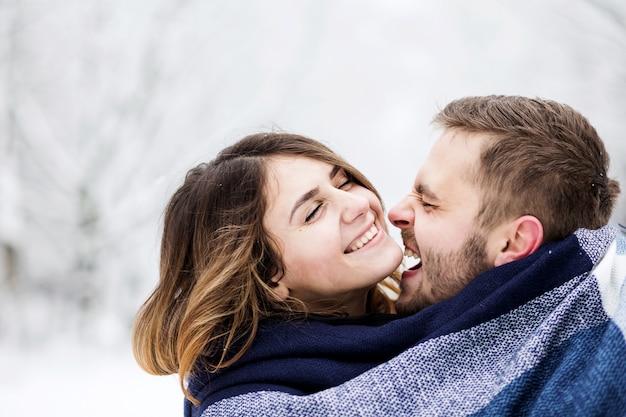 Para zakochanych jest owinięta w niebieski szalik wśród ośnieżonego parku