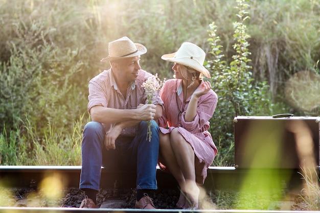 Para zakochanych kowbojów z walizką w pobliżu kolei