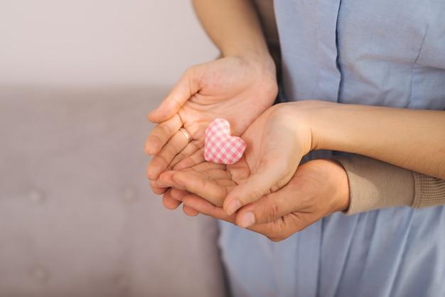 Para zakochanych. mężczyzna i kobieta ręka trzyma kształt serca.