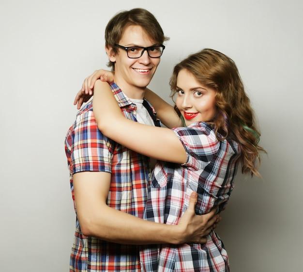 Para zakochanych. młoda kobieta i mężczyzna ubrany na co dzień na szarym tle.