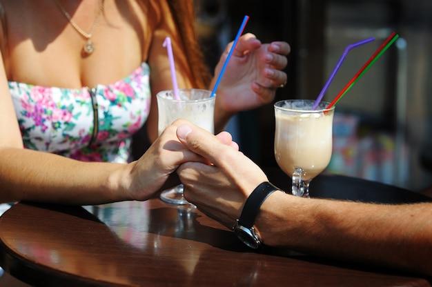 Para zakochanych pije kawę w kawiarni, trzymając się za ręce