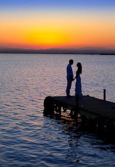 Para zakochanych podświetlenie sylwetka nad jeziorem