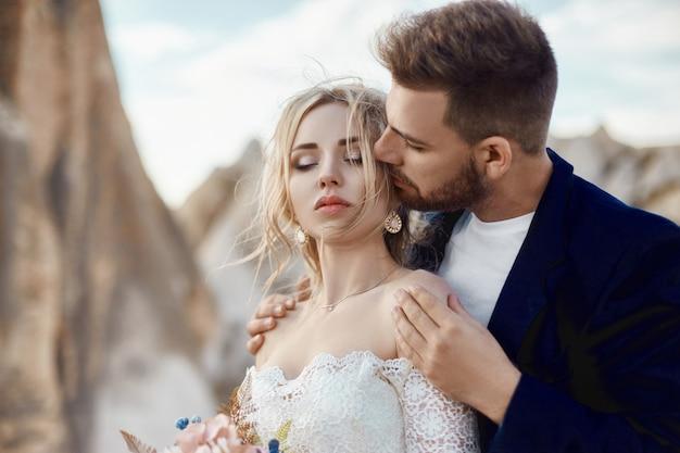 Para zakochanych przytula i całuje w bajecznych górach w naturze. dziewczyna w długiej białej sukni z bukietem kwiatów w dłoniach, mężczyzna w kurtce. ślub w naturze, relacje i miłość