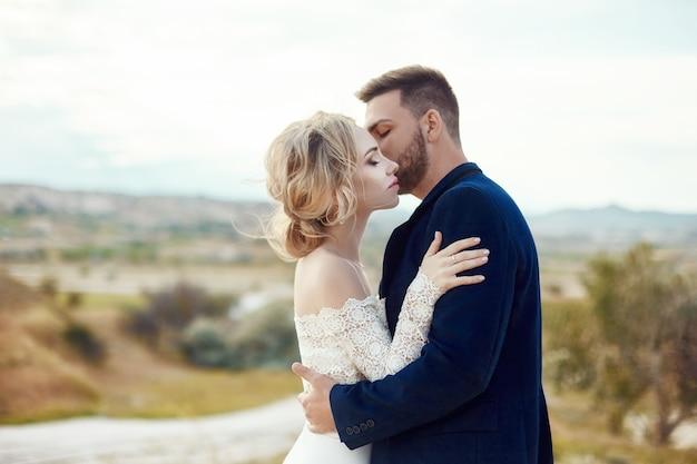 Para zakochanych przytula i całuje w bajecznych górach w naturze. kobieta w długiej białej sukni z bukietem kwiatów w dłoniach, mężczyzna w kurtce. ślub w naturze, relacje i miłość