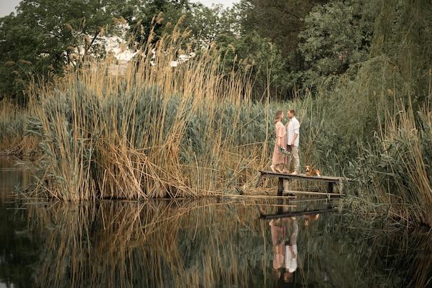 Para zakochanych przytula na drewnianym molo w przyrodzie.