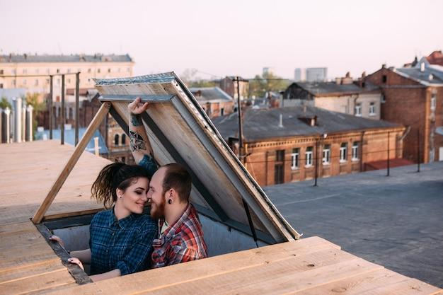 Para zakochanych. romantyczna randka na dachu. twórczy czas wolny, scena filmowa. szczęśliwi i młodzi uśmiechnięci ludzie skupieni na pierwszym planie, w tle miejskim
