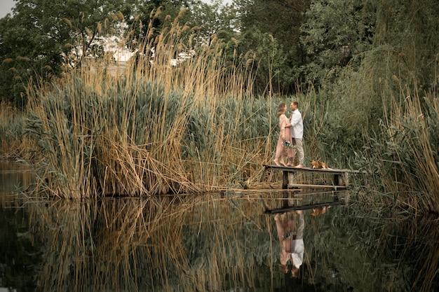 Para zakochanych ściska i całuje na drewnianym molo w przyrodzie.
