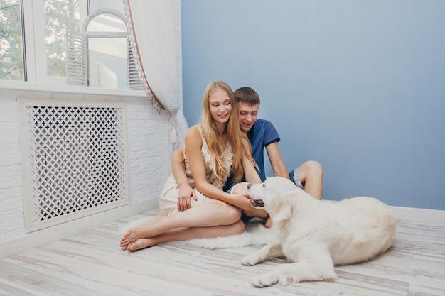 Para zakochanych siedzi w domu na podłodze ze swoim psem. miłośników mężczyzny i kobiety, przytulanie na podłodze