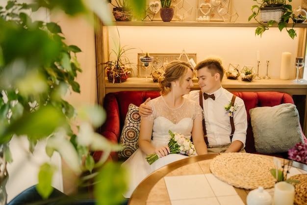 Para zakochanych siedzi w kawiarni, pan młody ściska pannę młodą za ramię, pochyla głowę w głowie panny młodej, para zakochana w dniu ślubu