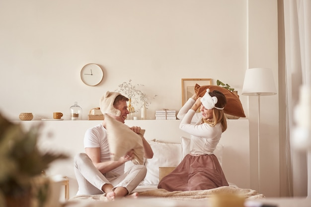 Para zakochanych, śmiejąc się i grając na łóżku. mężczyzna i kobieta walczą poduszki. młoda szczęśliwa para pokonała poduszki na łóżku w sypialni w domu