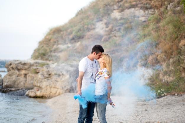 Para zakochanych stoi na brzegu i całuje się, trzymając w rękach niebieski dym