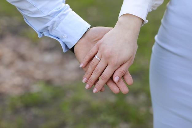 Para zakochanych trzymać ręce w zielonym polu w lecie. zdjęcie z bliska