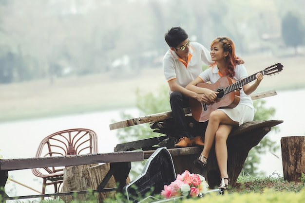 Para zakochanych w grze na gitarze w przyrodzie