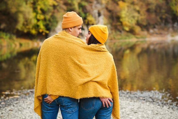 Para zakochanych w jesiennej przyrody. miłośnicy romantycznych randek i wspólnej zabawy na świeżym powietrzu. chłopak z dziewczyną na spacerze w pobliżu jeziora jesienią.