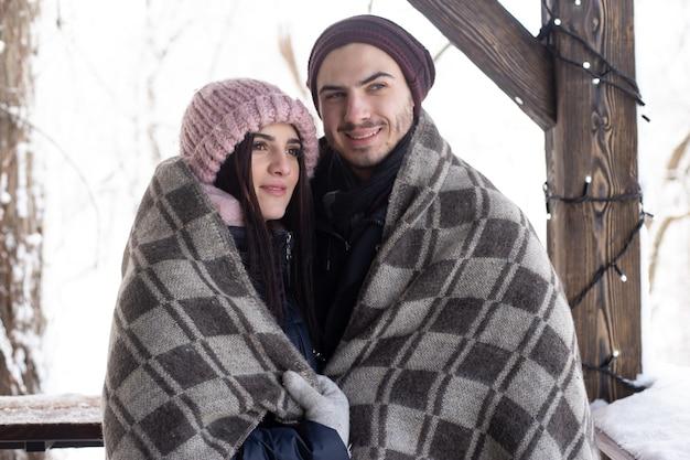 Para zakochanych w koc spędzać czas razem w parku ze śniegiem