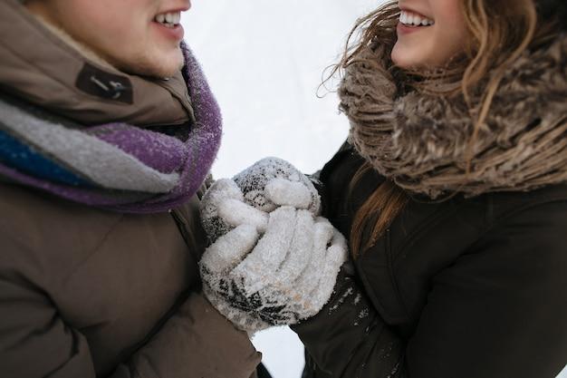 Para zakochanych w zimowy zimowy dzień w zimowe mitenki, ogrzewa trzymając się za ręce. zimowy