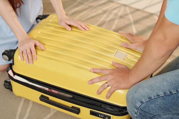 Para zamykająca razem walizkę