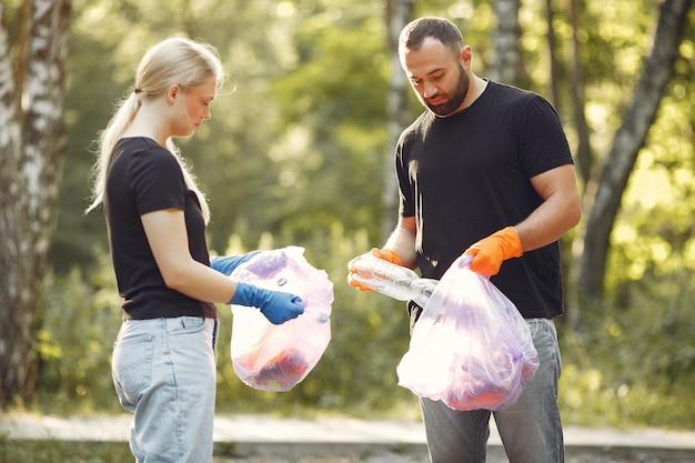 Para zbiera śmieci w workach na śmieci w parku