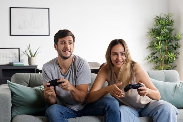 Para ze średnim strzałem grająca w gry na kanapie