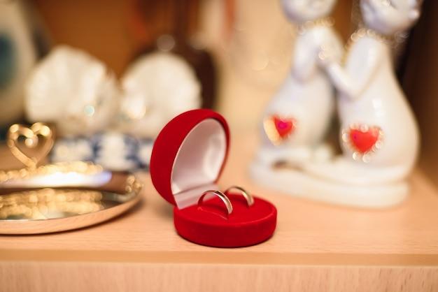 Para złotych obrączek ślubnych leży w czerwonym pudełku