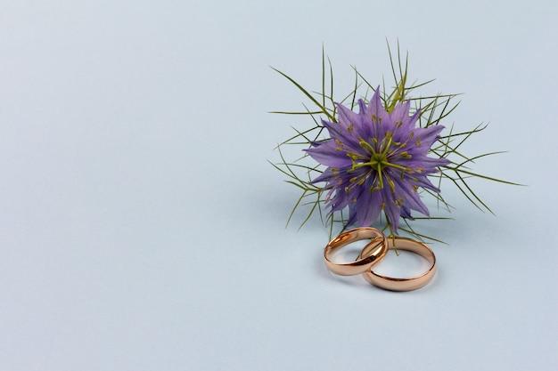 Para złotych obrączek ślubnych z niebieskim kwiatem na niebieskim tle z miejscem na kopię