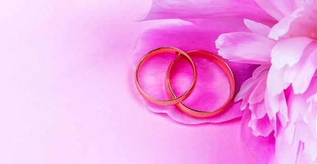 Para złotych obrączek ślubnych z różowym kwiatem piwonii na różowym tle z miejscem na kopię