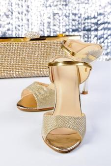 Para złotych sandałów na wysokim obcasie, ze złotą kopertówką na stole