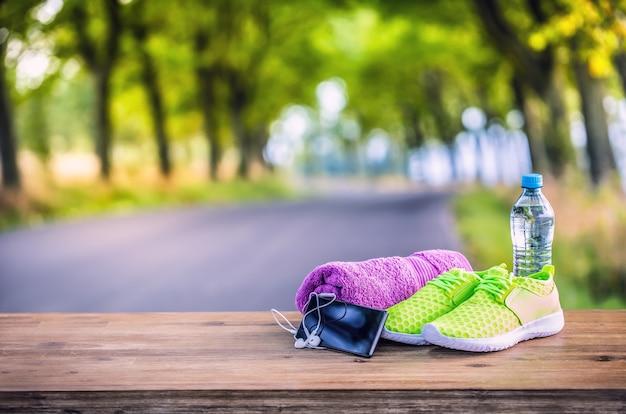 Para żółto-zielonych butów sportowych ręcznik wody inteligentny pone i słuchawki na desce. w tle leśny lub parkowy szlak. akcesoria do biegania sportowego.