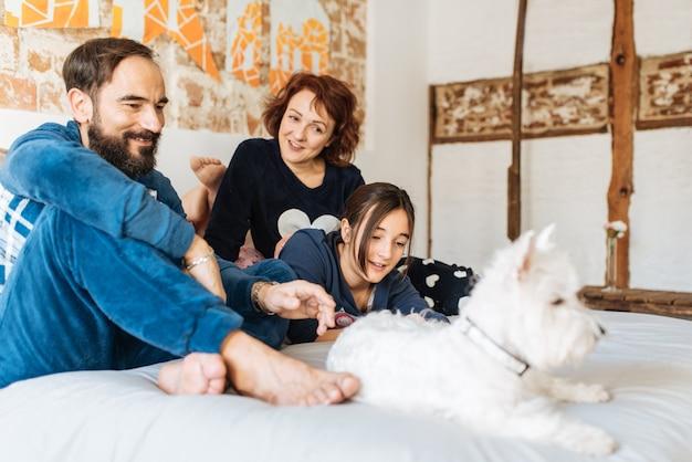 Para zrelaksowała się w domu w łóżku z małą córeczką i psem