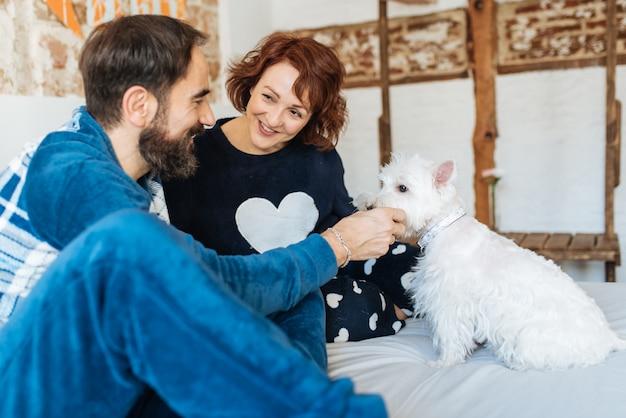 Para zrelaksowana w domu w łóżku z psem
