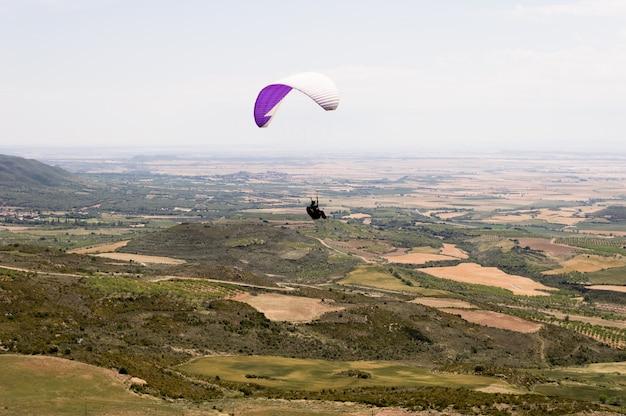 Paraglider sylwetka lata nad doliną w loarre, huesca, hiszpania.