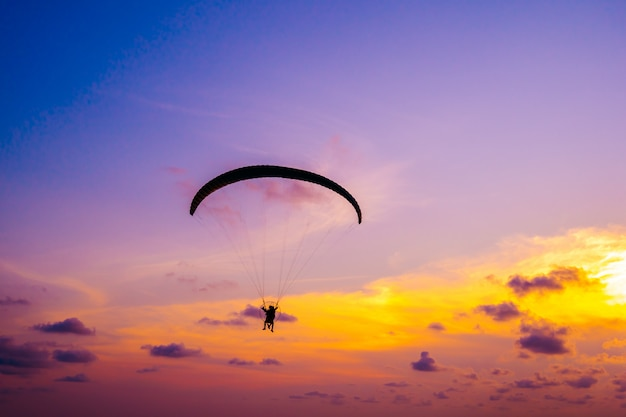 Paralotnia latająca na niebie o zachodzie słońca