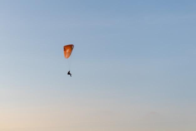 Paralotnia latające nad te brzeg o zachodzie słońca. sport paralotniowy