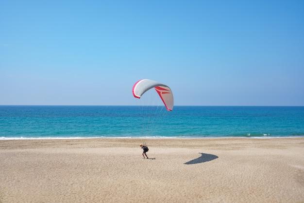 Paralotnia leci nad brzegiem morza z błękitną wodą i niebem na horyzoncie. widok na paralotnię i błękitną lagunę w turcji.