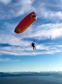 Paralotnia leci po błękitnym niebie na tle chmur.