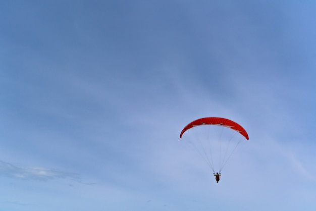 Paralotnia na czerwonym paralotni lata nad morzem