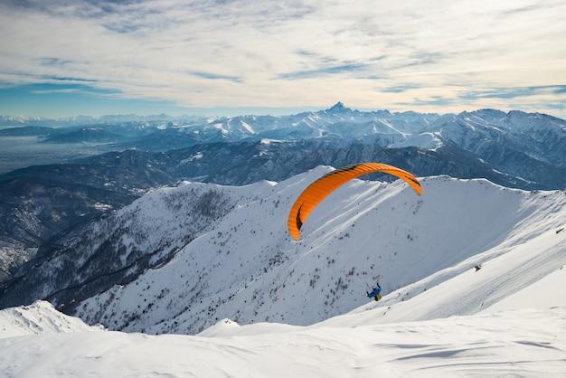 Paralotnia startuje z zaśnieżonego stoku