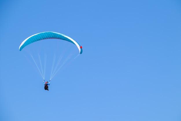 Paralotnia szybująca na niebieskim niebie.