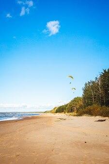 Paralotnia z jasnożółtym spadochronem na tle błękitnego nieba