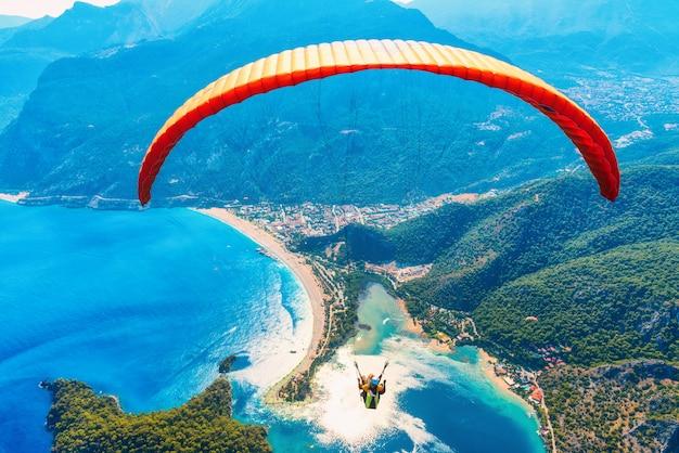 Paralotniarstwo na niebie. paralotnisty tandem lata nad morzem z błękitne wody i górami w jaskrawym słonecznym dniu.