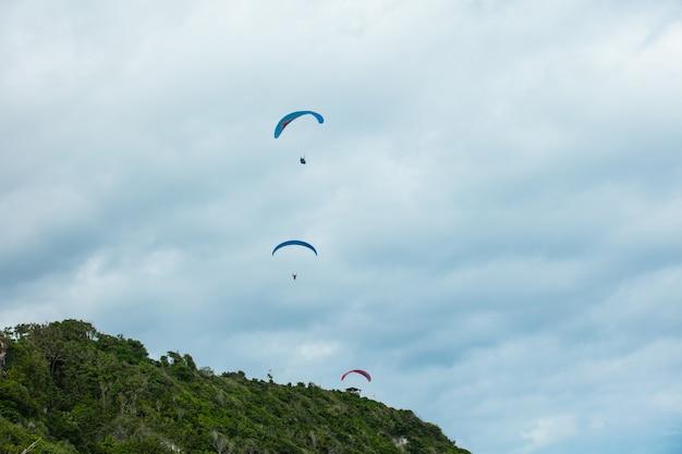 Paralotniarze startują z zielonej góry na tle błękitnego nieba z chmurami