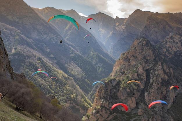 Paralotniarze szybujący wśród gór o zachodzie słońca
