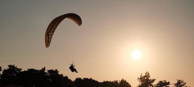 Paralotnie latają na tle słonecznego zachodu słońca. sporty lotnicze. aktywny wypoczynek poza miastem.