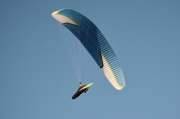 Paralotnie na tle błękitnego nieba. sporty lotnicze.. aktywny wypoczynek poza miastem.