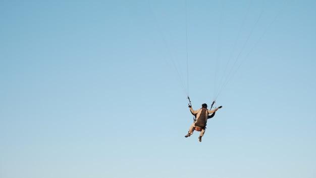 Paralotnie na tle błękitnego nieba. sporty lotnicze. aktywny wypoczynek poza miastem.