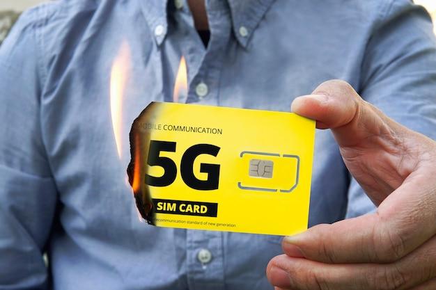 Paranoidalny mężczyzna pali kartę sim 5g ze strachu przed szkodliwym promieniowaniem. walka z szybkim internetem 5 g. wsteczny odmawia komunikacji mobilnej. zniszczenie technologii wieżowych 5p.