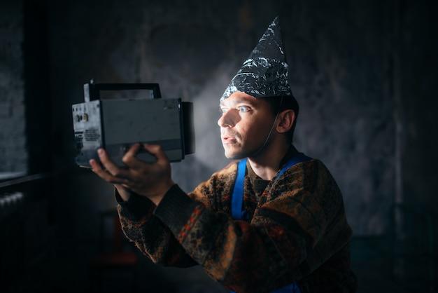 Paranoik w czapce z folii aluminiowej ogląda telewizję, ochrona umysłu przed telepatią, koncepcja paranoi. ufo-fobia, teoria spiskowa