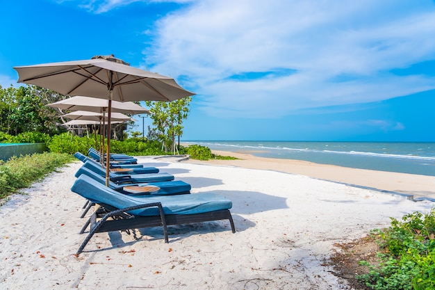 Parasol i krzesło na plażowym dennym oceanie z niebieskim niebem i biel chmurą